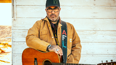 Aaron Lewis with his guitar in front of a house.