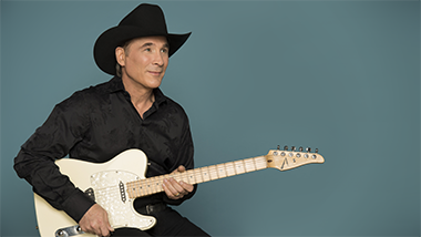 clint black sitting with a white guitar against a turquoise background