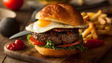 burger with fried egg and bacon with fries